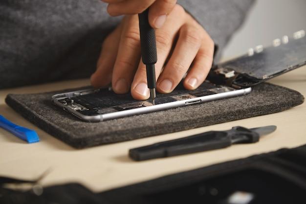 Master gebruikt stuurprogramma om schroeven in elektronische platen van smartphones los te draaien om het te repareren, close-up