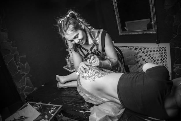 Master in de kunst van het tatoeëren richt zich op haar werk in de tattoo-studio