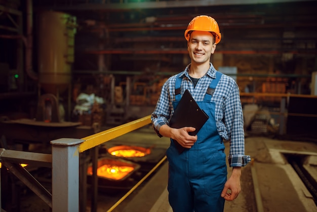 Master in helm in oven met vloeibaar metaal, staalfabriek, metallurgische of metaalverwerkende industrie, industriële productie van ijzerproductie op molen