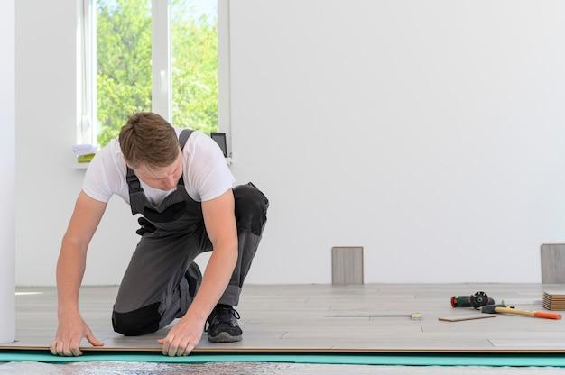 Master in uniform van werknemers legt het laminaat in witte kamer man nieuwe gelamineerde houten vloer installeren
