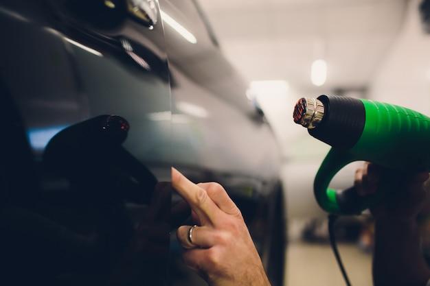 Master installeert tintfolie voor auto met haardroger. concept bescherming auto