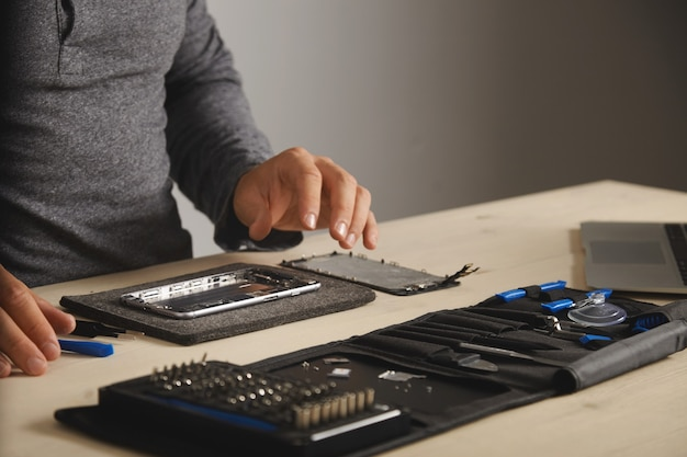 Master is klaar om de telefoon te monteren en te repareren door een nieuwe batterij en scherm te vervangen, zijaanzicht