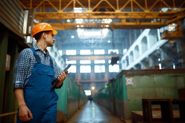 Master kijkt naar het werk van de kraanmachinist op de metaalfabriek. metaalverwerkende industrie, industriële fabricage van staalproductie