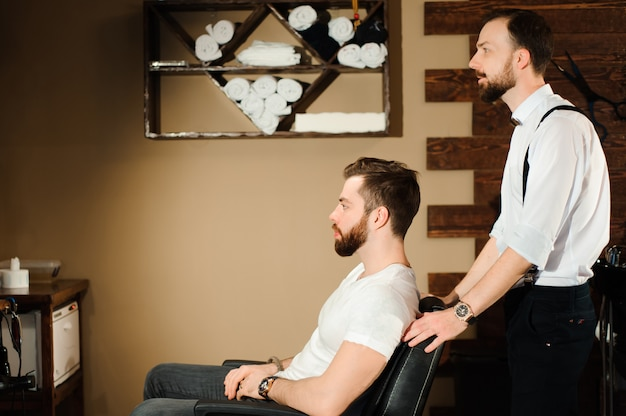 Master knipt haar en baard van mannen in de kapperszaak