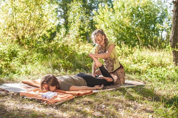Master massagetherapeut past haar massagevaardigheden toe op haar cliënt op de grond. Premium Foto