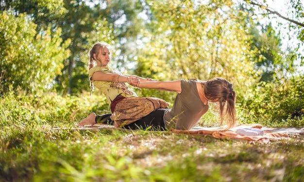 Master massagetherapeut voert adequaat een geweldige massage in de natuur uit.