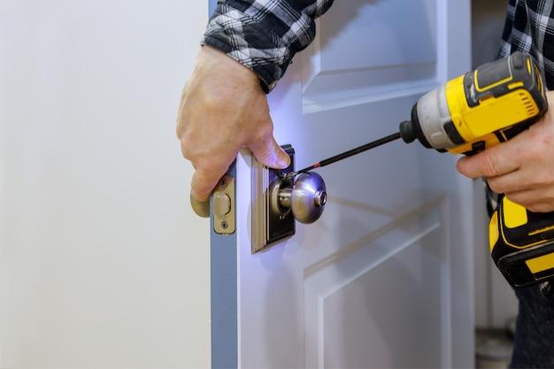Master met schroevendraaier installeert toegang tot de kamerdeur nieuw slot in huis.