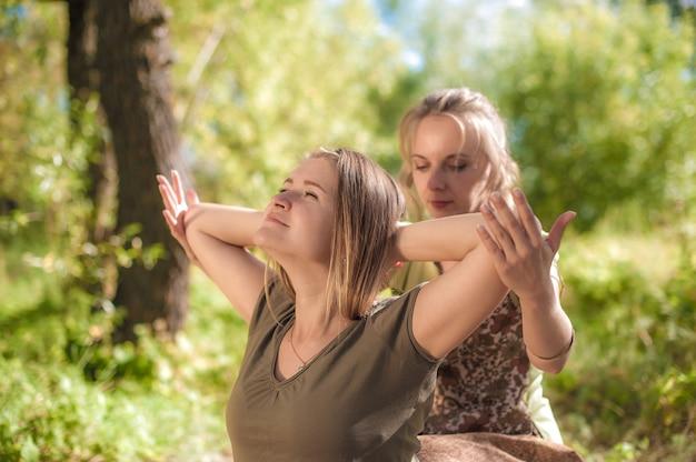 Master of massage past haar massagevaardigheden toe op haar cliënt in het bos
