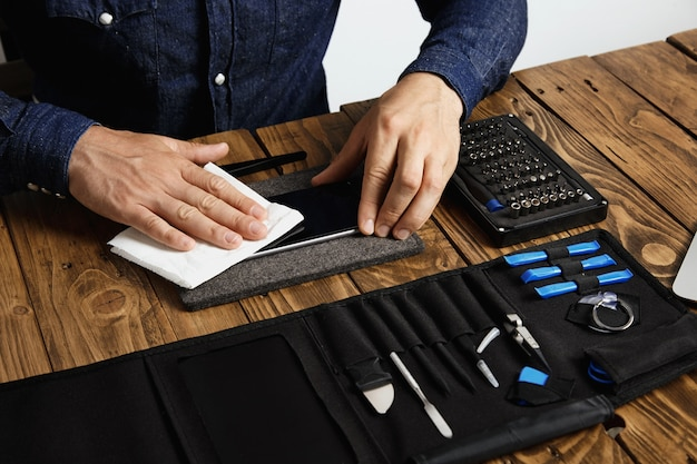 Master reinigt mobiele telefoon na succesvolle restauratie met witte doek in de buurt van zijn professionele instrumenten in gereedschapstas op houten tafel