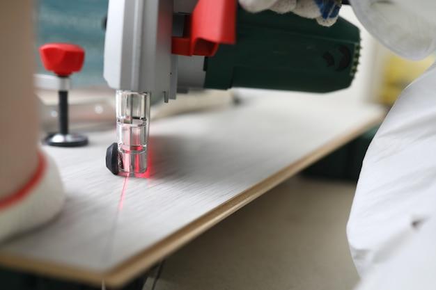 Master snijdt laminaat met lasersnijmachine.