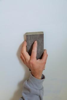 Master stukadoor effent de naden met pleister tussen gipspanelen op de muur.