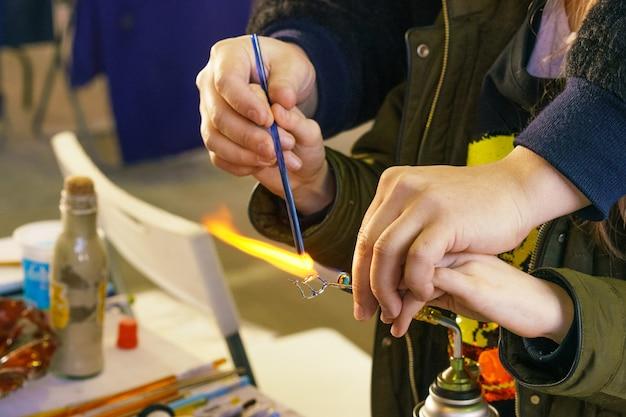 Masterclass over het maken van decoratief speelgoed van glas, de leraar laat zien hoe je kunt smelten en maken