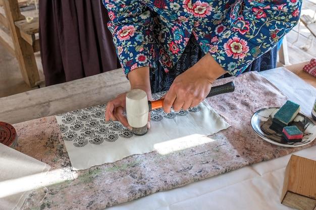 Masterclass over het tekenen van een patroon op een stof handmatige afwerking van textiel met een stempel