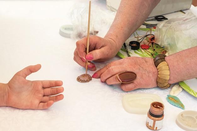 Masterclass sieraden maken een vrouw leert een kind een broche maken met een inscriptie