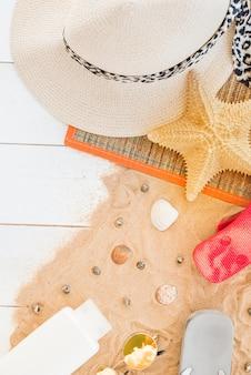 Mat met hoed en zeester dichtbij zeeschelpen en fles op zand