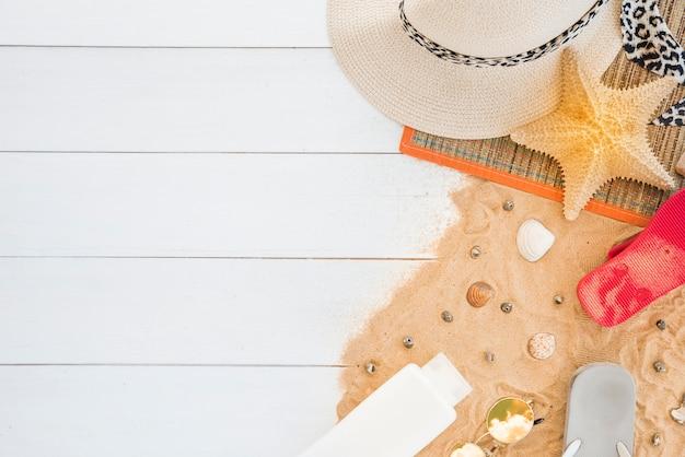 Mat met hoed en zeester dichtbij zeeschelpen en lotion op zand