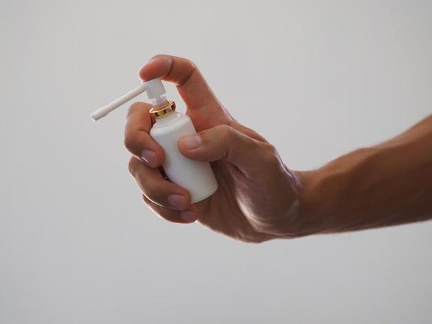 Mat plastic fles met lange en korte spuitmond voor orale spray in de hand.
