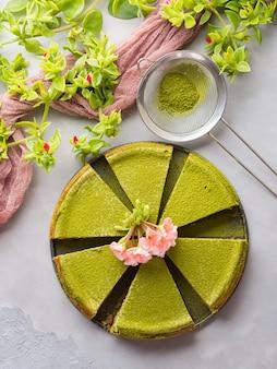 Matcha gebakken kaastaart en roze bloemen