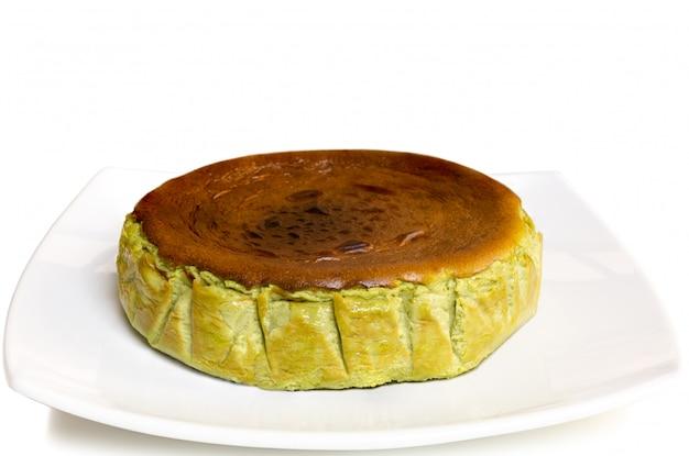 Matcha groene thee baskische gebrande kaastaart die op witte achtergrond wordt geïsoleerd.
