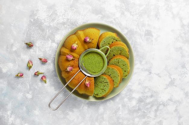 Matcha groene thee bundt cake op grijze steen bovenaanzicht exemplaarruimte