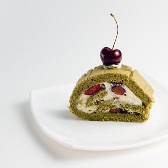 Matcha groene thee cake versierd met een kers op de bovenkant