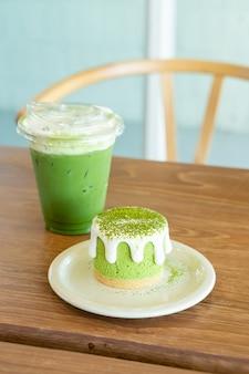 Matcha groene thee cheese cake met groene thee beker op tafel in café-restaurant