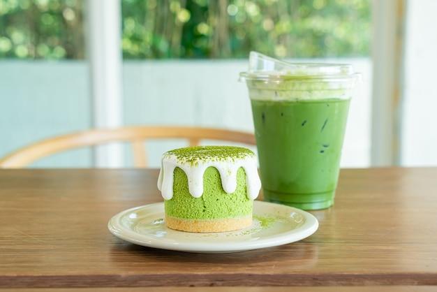Matcha groene thee cheesecake met groene thee beker op tafel in café-restaurant