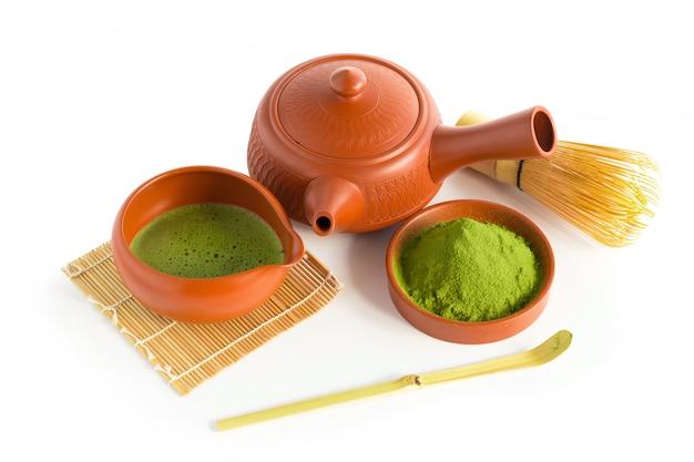 Matcha groene thee en japanse theeset. ceramische theepot en een stomende kop die op witte achtergrond wordt geïsoleerd