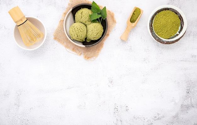 Matcha groene thee-ijs met wafel kegel setup op witte steen.