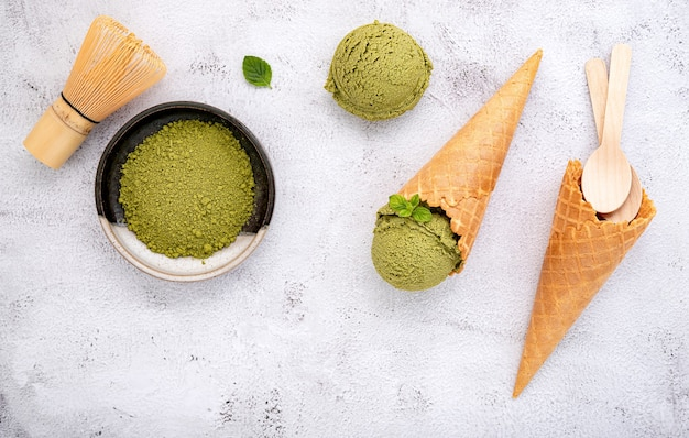 Matcha groene thee-ijs met wafelkegel en muntblaadjes setup op witte steen.
