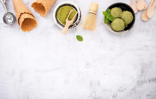 Matcha groene thee-ijs met wafelkegel en muntblaadjes setup op witte stenen achtergrond.