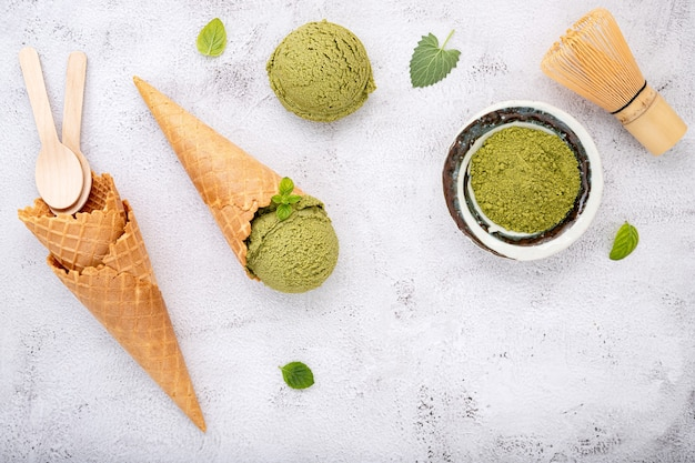Matcha groene thee-ijs met wafelkegel en muntblaadjes setup op witte stenen achtergrond