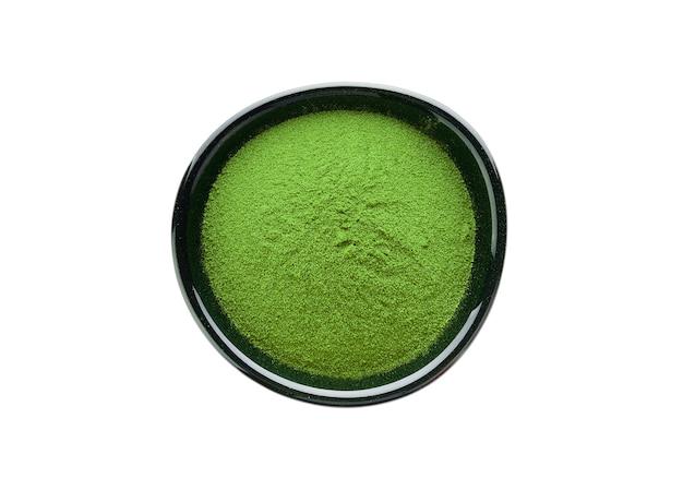 Matcha groene thee in poedervorm in een kom, geïsoleerd op wit