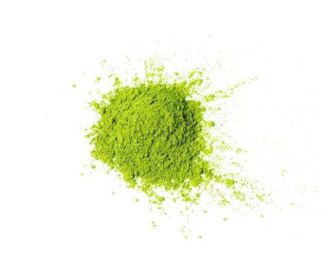 Matcha groene thee in poedervorm verspreid over de witte ruimte bovenaanzicht kopie ruimte