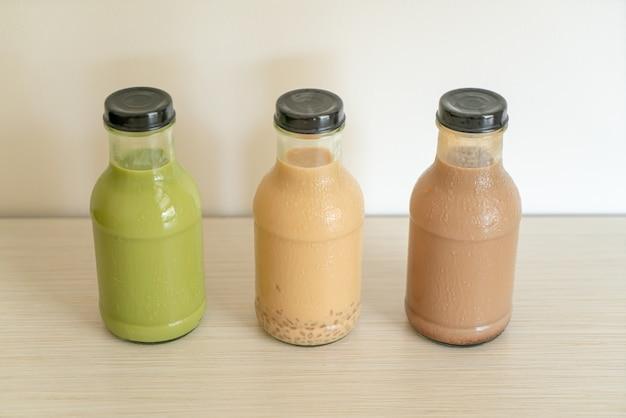 Matcha groene thee latte, chocolade en melkthee met puddinggelei in glazen fles op tafel