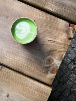 Matcha groene thee latte in beschikbare karton meeneemkop op rustieke houten lijst in openlucht