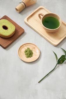 Matcha groene thee latte in een kopje en theeceremonie gebruiksvoorwerpen met duitse cake. ruimte kopiëren