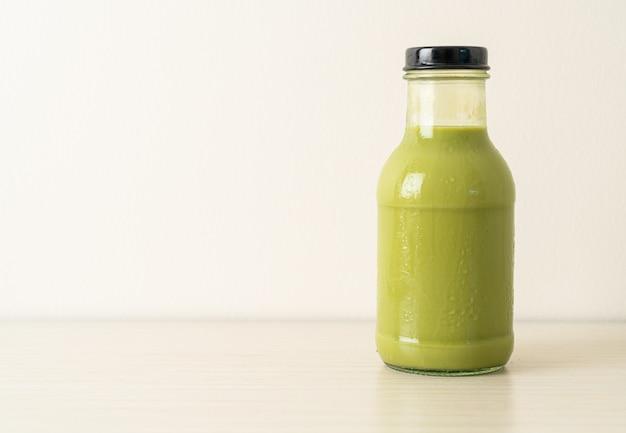 Matcha groene thee latte in glazen fles op tafel