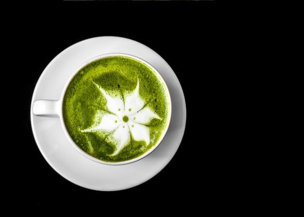 Matcha groene thee latte kunst in kop op witte schotel tegen zwarte achtergrond