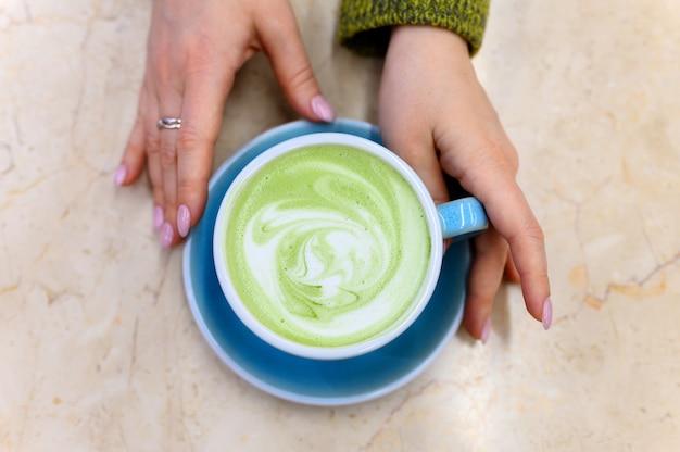 Matcha groene thee latte met een patroon van melkschuim in een blauwe keramische beker en vrouwenhanden op tafel