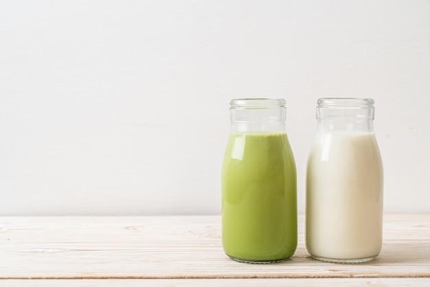 Matcha groene thee latte met verse melk in fles op hout