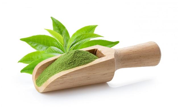Matcha groene thee poeder in houten lepel met blad op wit