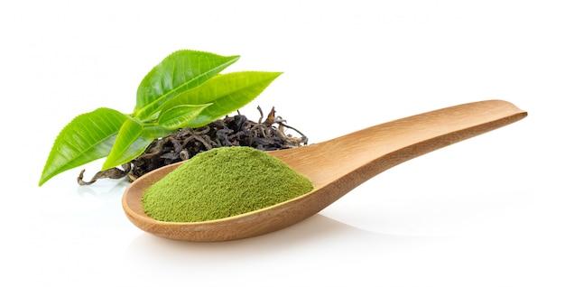 Matcha groene thee poeder in houten lepel. vers groen theeblad en droog op wit