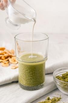 Matcha met melk op een grijze achtergrond naast fruitchips. ontbijt concept