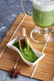 Matcha-poeder in groene thee in kom en matcha latte op grijze tafel
