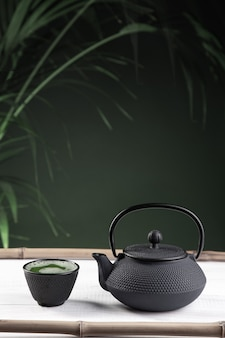 Matcha thee en theepot op groene achtergrond op witte houten basis. traditionele japanse drank. verticaal formaat.