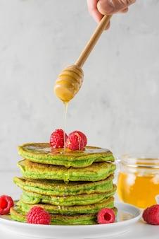 Matcha thee groene pannenkoeken. stapel zelfgemaakte pannenkoeken met verse frambozen en vloeiende honing. verticale oriëntatie
