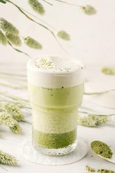 Matcha-thee in een glas op een lichte achtergrond.