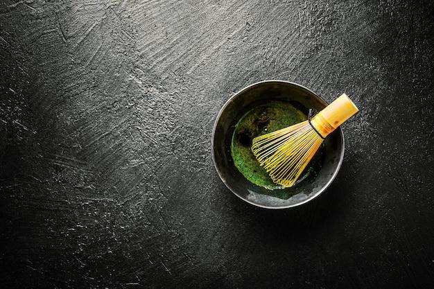 Matcha-thee in zwarte kom op donker