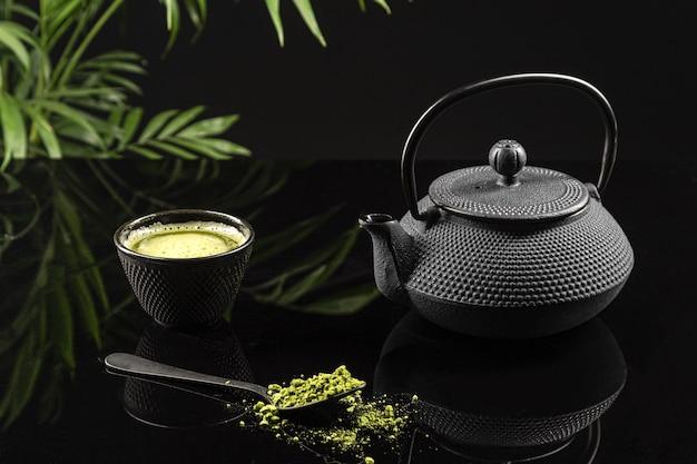 Matcha thee poeder en thee accessoires op zwarte achtergrond. thee ceremonie. traditionele japanse drank.